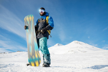 A professional snowboarder stands with his snowboard Wall mural