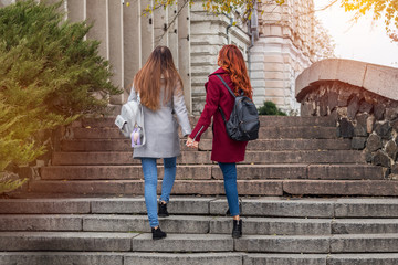 Two female teenagers walking up the stone steps holding hands in the autumn city.
