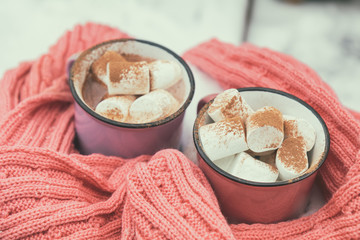 Hot chocolate with marshmallow in pink and violet two cups wrapped in a cozy winter pink scarf on the snow-covered table in the garden. Coloring and processing photo small depth of field