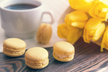 Beautiful spring music background. Cup of coffee, macaroons, yellow tulips, musical page on a dark wooden background. Shallow depth of field. Coloring photo with soft focus in instagram style
