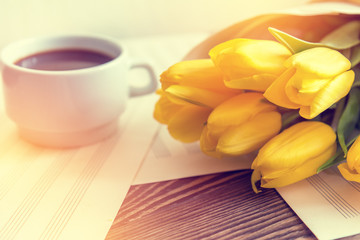 Beautiful spring music background. Cup of coffee, yellow tulips, musical page on a dark wooden background. Shallow depth of field. Coloring photo with soft focus in instagram style