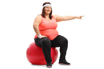 Overweight woman sitting on a pilates ball and pointing