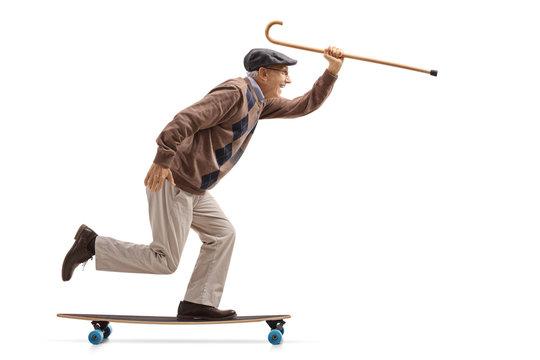Joyful senior holding a cane and riding a longboard