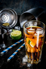 Cuba Libre, long island or iced tea cocktail with strong alcohol, cola, lime and ice, two glass, dark background copy space