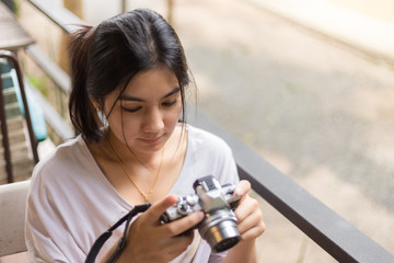 Asian woman holding mirrorless camera in the coffee cafe