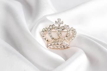 Wall Mural - golden brooch crown isolated on white silk