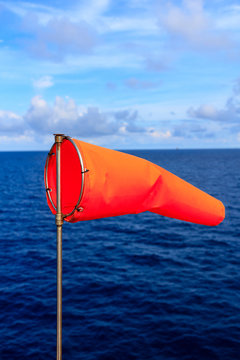 Orange wind sock in blue sky and blue sea with white cloud background.