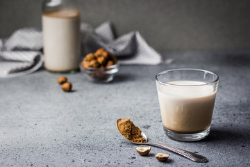 Homemade vegan nut milk in a glass on concrete background. Selective focus, copy space, close up.