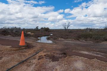 Strassenschaden einer Landstrasse durch Hochwasser / Regenzeit im Outback von West-Australien mit Warnkegel und Restwasser im Hintergrund