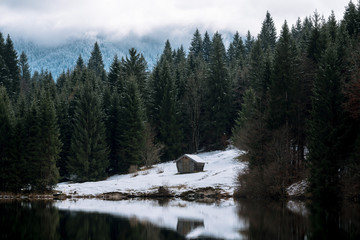 Lake Geroldsee overlooking a forest with cabin with the Karwendel Mountains in Background in Bavaria, Germany in winter