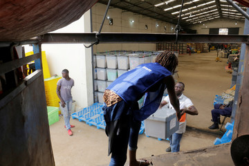 Election worker moves boxes of voting materials at the National Elections Commission headquarters in Monrovia