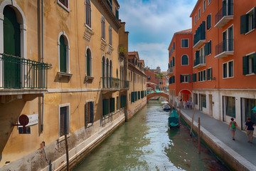 Traditional narrow canal street with gondolas and old houses in Venice, Italy. Architecture and landmarks of Venice. Beautiful Venice postcard.