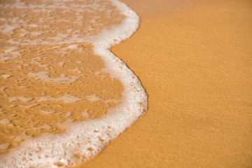 Background. A close-up of a wave runs over a sandy beach