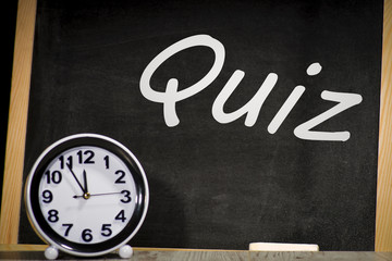 Quiz concept, inscription on a chalkboard and clock.