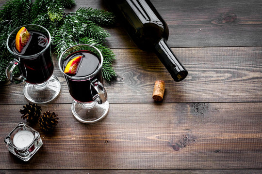 Warm mulled wine with citrus and spices for winter evening near spruce branch on dark wooden background copyspace