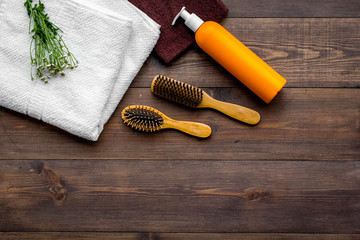 Product's for daily hair care. Comb, shampoo, towel on dark wooden background top view copyspace
