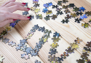 female hand piles puzzles on a wooden background