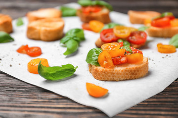 Tasty bruschetta with tomatoes on parchment, closeup