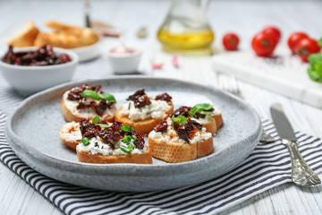 Tasty bruschettas with sun-dried tomatoes on plate, closeup
