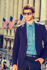 Serious European businessman in New York. Dressing in blue suit, shirt, wearing sunglasses, a young handsome guy with beard standing in business district, looking down, thinking. Filtered effect..
