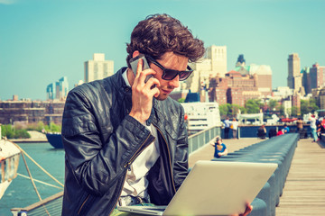 Businessman traveling, working in New York. Wearing sunglasses, a young guy with beard, sitting on bench at harbor, working on laptop computer, talking on phone in the same time. Filtered effect..