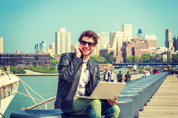 Businessman enjoying working on site. Wearing leather jacket, sunglasses, a guy with beard, sitting on bench at harbor, working on laptop computer, talking on phone in the same time. Filtered effect..