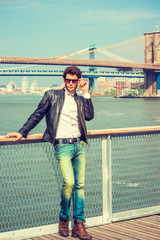 European man traveling in New York, wearing black leather jacket, white shirt, blue jeans, brown boot shoots, sunglasses, standing at harbor, thinking. Manhattan, Brooklyn bridges on background.