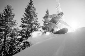 Low angle monochrome shot of a freeride snowboarder riding the slope copyspace extreme winter sports adrenaline activity lifestyle sportspeople concept
