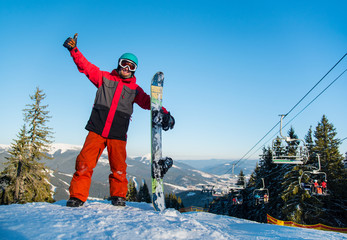 Freerider snowboarder smiling to the camera, showing thumb up, standing to the top of the mountain with his snowboard, copyspace ski-lift people lifestyle winter holidays vacation tourism resort