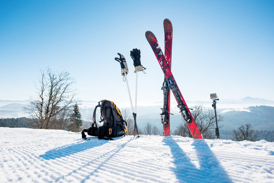 Shot of skiing equipment on top of the ski slope in the mountains winter sports skis backpack travelling lifestyle extreme active living concept