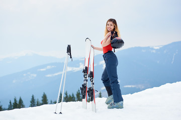 Attractive lady skier wearing ski pants and red bodice, smiling to the camera, standing on the top of the snowy slope with ski equipment at winter ski resort in the mountains