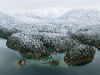 Lake Eibsee during Winter with snowy forests and calm islands in the water, Bavaria Germany