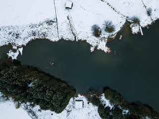 Aerial of Lake Geroldsee in Bavaria with forest and cabin, Germany during winter
