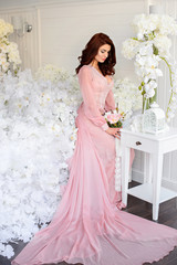 Pretty woman in a beautiful dress, with flowers