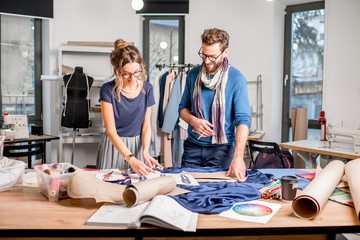 Couple of fashion designers working with fabric and clothing sketches at the studio full of tailoring tools and equipment