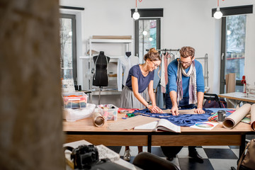 Couple of fashion designers working with fabric at the studio full of tailoring tools and equipment Wall mural