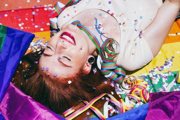Mujer joven y pelirroja muy alegre en una fiesta y tumbada sobre una bandera arco iris