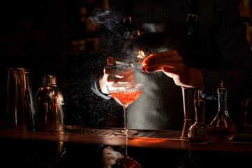 Tuinposter Cocktail Bartender setting fire to sweet cocktail in bocal