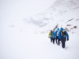 Mountaineers team walks in fresh snow during a winter expedition. West italian Alps, Europe.