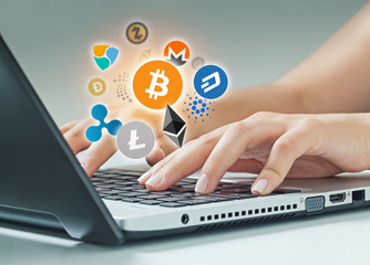 female hands typing on laptop. Bitcoin, ethereum and altcoin logos flying on air. cryptocurrency concept