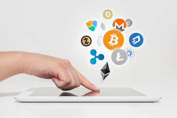woman hand touching tablet computer. Bitcoin, ethereum and altcoin logos flying on air