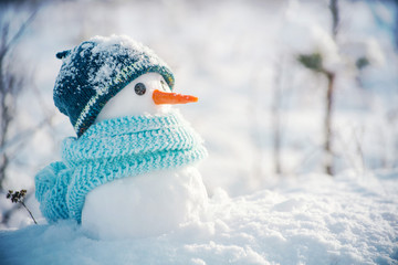 Little snowman in a cap and a scarf on snow in the winter. Festive background with a lovely snowman. Christmas card, copy space
