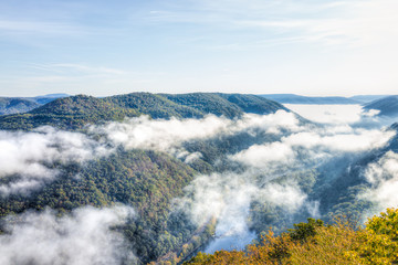 Mountains and fog, mist clouds in morning floating above forest trees, covering, blanketing valley in Grandview Overlook, West Virginia