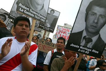 People holding pictures of victims of the guerrilla conflict in the 80s and 90s march after Peruvian President Kuczynski pardoned former President Fujimori in Lima