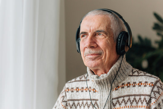 Handsome Senior man listening music in headphones