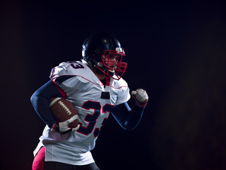 American football player holding ball while running on field