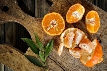 Fresh clementines freshly picked in slices and in wedges on wooden background
