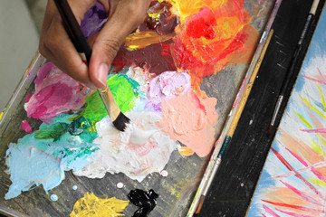 artists mixing color on wooden palette