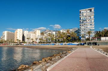 Sand coastline with promenade in Marbella town at Costa del Sol, Andalusia, Spain