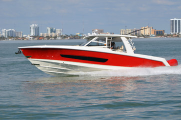 Well appointed sports fishing boat, red with white trim,cruising on the florida intra-coastal waterway off Miami Beach.